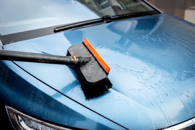 Proces van autowassen met schuimborstel.