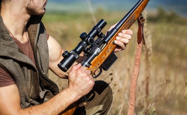 Proces van de jacht tijdens het jachtseizoen. mannelijke jager klaar om te jagen. detailopname. de man is op jacht, sport. jager man. jacht periode. man met een pistool, geweer. de mens laadt een jachtgeweer op.