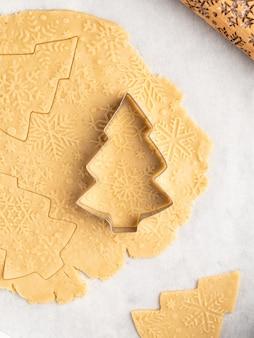 Proces van het bakken van traditioneel kerst- en nieuwjaarsdessert, peperkoekkoekjes, deegrol met sneeuwvlokkenpatroon, anijssterren en kaneel, kerstmis en winter, frame-indeling