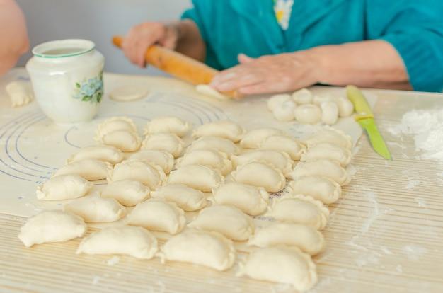 Proces van het beeldhouwen van zelfgemaakte pierogi. oma bereidt een nationaal oekraïens gerecht voor - vareniki.
