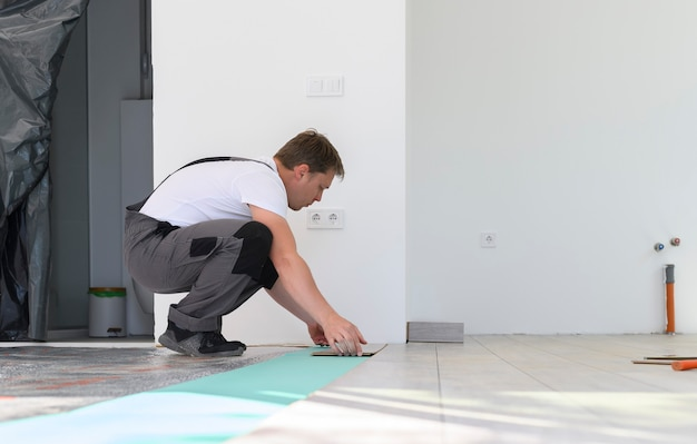 Proces van het leggen van laminaat in witte kamer man in uniform nieuwe gelamineerde houten vloerzijde installeren floor