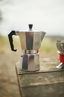 Proces van het maken van campingkoffie buiten met een metalen geiser koffiezetapparaat op een gasbrander, stap voor stap.