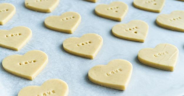 Proces van het maken van hartvormige koekjes met het woordliefde klaar om te bakken. gebak concept.