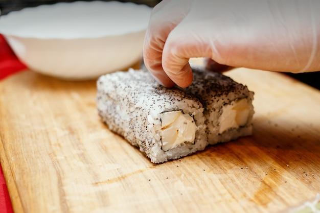 Proces van het maken van sushi, vreemd sushibroodje met papaver op houten bureau