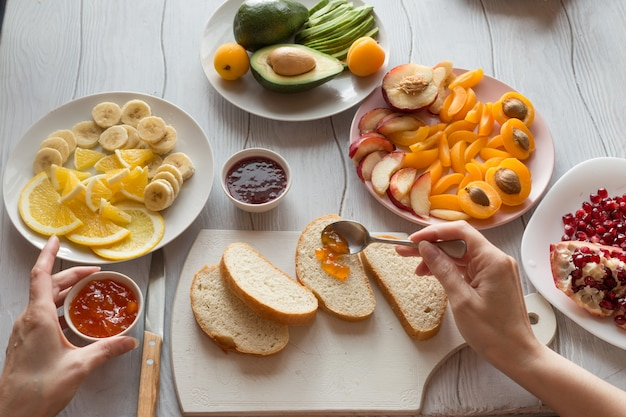 Proces van het maken van zoete toast met jam en diverse fruit abrikozen, perziken, bananen, sinaasappels en avocado versierd met granaatappels bovenop.