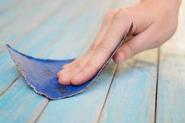 Proces van het met de hand poetsen van houten plankoppervlak met een schuurpapier