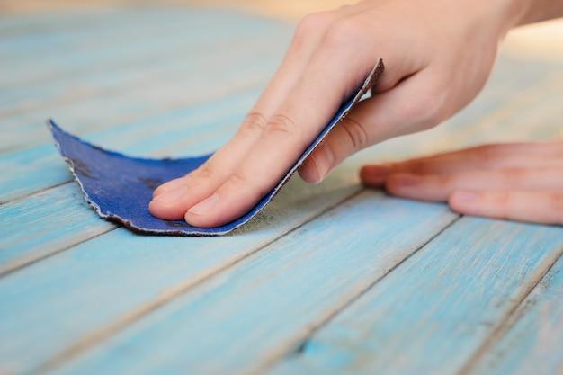 Proces van het met de hand polijsten van houten plankoppervlak met een schuurpapier