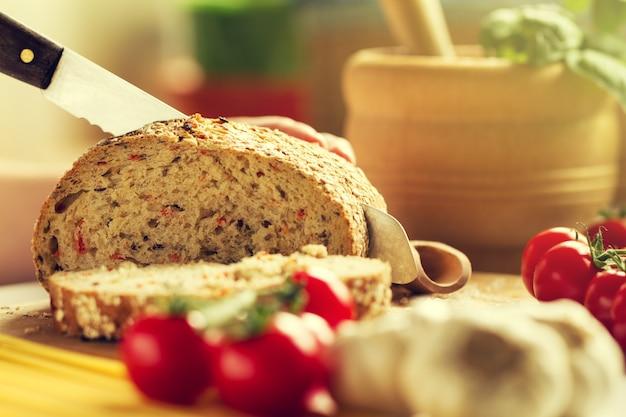 Proces van het snijden van volkorenbrood in de keuken. keukenachtergrond. kookproces. afgezwakt.