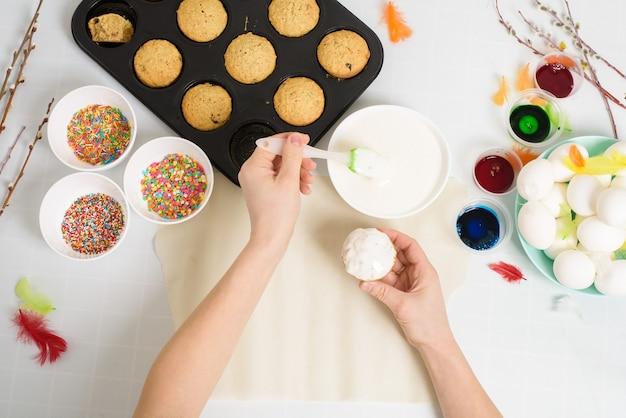 Proces van het verfraaien van mini cupcakes pasen taarten met wit suikerglazuur en zoete snoepjes, bovenaanzicht