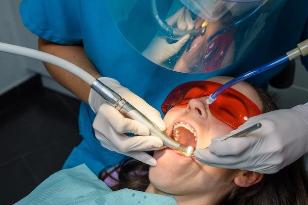 Proces van het verwijderen van beugels van een blank meisje in een tandheelkundige kliniek met een vrouwelijke tandarts