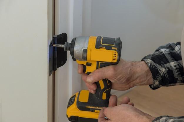 Proces van installatie roestvrijstalen deur scharnieren op een witte houten deur met schroevendraaier