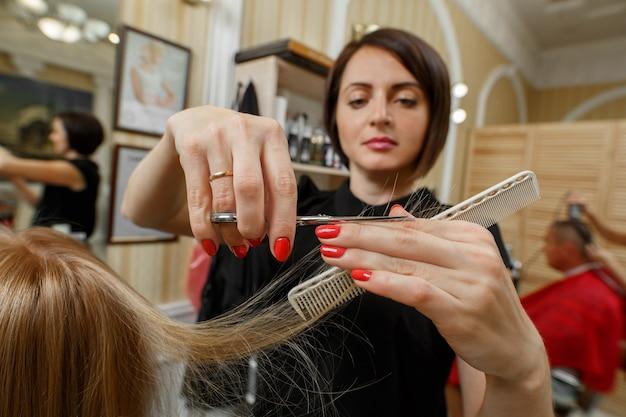 Proces van kapsels. kapper met een schaar en kam in de handen close-up. kapper zal de uiteinden van het goed verzorgde blonde haar knippen. haar meester.