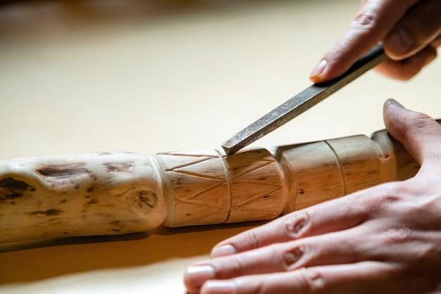 Proces van man maken van houten wandelstok binnenshuis tijdens quarantaine.