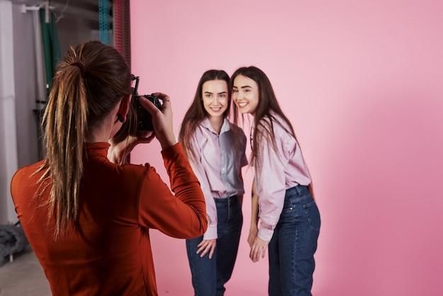 Proces van vastleggen. foto van twee meisjes die gefotografeerd door vrouwelijke cameraman in de studio