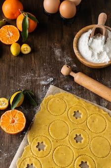 Proces van voorbereiding zelfgemaakte traditionele kerst linzer koekjes, koekjesdeeg, deegrol, bloem en mandarijnen op houten tafel