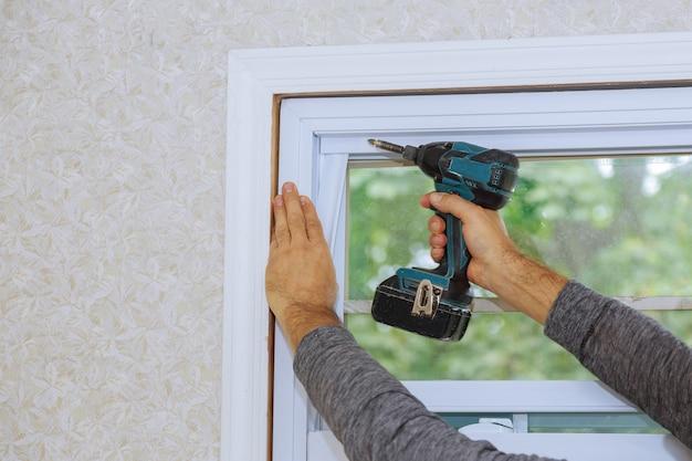 Proces van werknemer die nieuw plastic pvc-venster installeert met behulp van een schroevendraaier