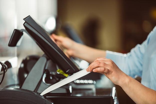 Proces voor het afdrukken van factuur voor een klant, creditcardverwerker, bonprinter met papieren winkelrekening en touchscreen-monitor, pos