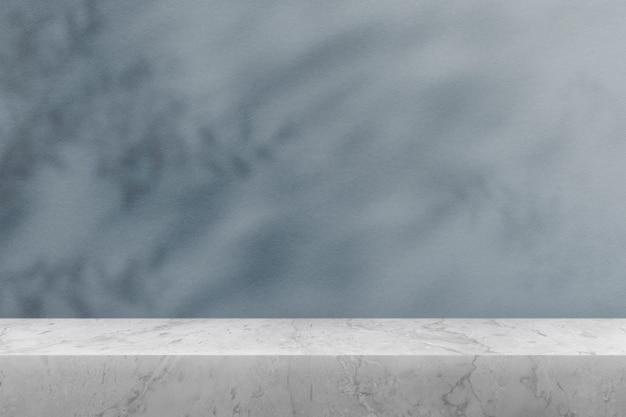Productachtergrond, leeg marmeren tafelblad met blauwe muur en plantenschaduw