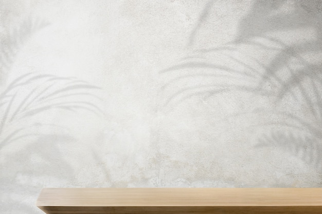 Productachtergrond, lege houten tafel met betonnen muur en plantenschaduw