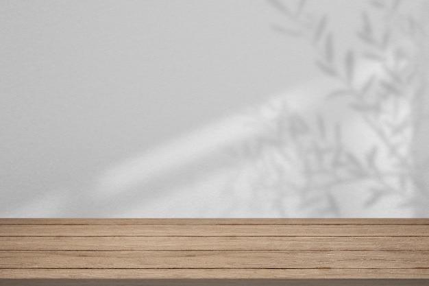 Productachtergrond, lege houten vloer met bladerenschaduw