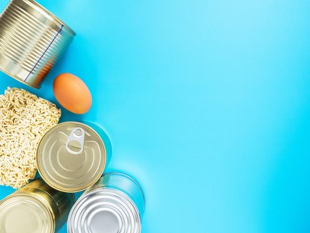 Producten van snelle voorbereiding en lange opslag geïsoleerd op blauwe achtergrond, copyspace. concept: voorraden voedseltavars voor de periode van quarantaine in het coronavirus en grieppandemie. voedsellevering.
