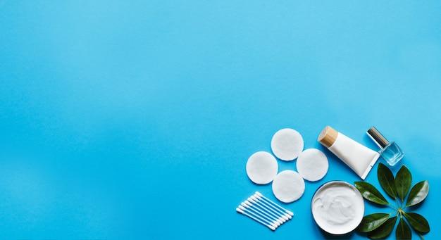 Producten voor dagelijkse hygiëne en huidverzorging op een pastelblauwe tafel met bovenaanzicht. natuurlijke cosmetica.