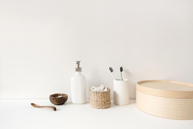Producten voor de ochtendroutine voor schoonheid en gezondheidszorg. spa, wellness, essentiële behandelingen. tandenborstels, oorstokken, vloeibare zeepcrème op witte tafel.