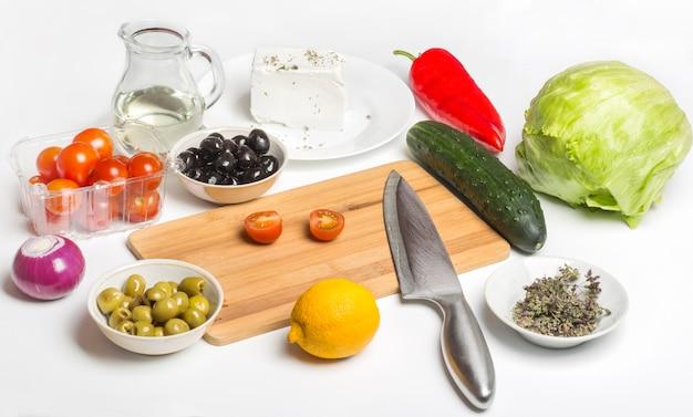 Producten voor griekse salade op een witte achtergrond.