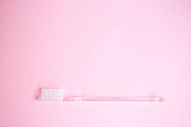 Producten voor persoonlijke verzorging van bovenaf bekijken. transparante tandenborstel op roze achtergrond