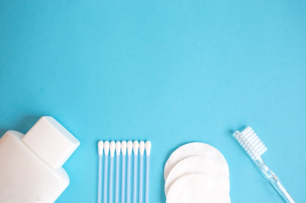 Producten voor persoonlijke verzorging. witte fles, oorstokken, wattenschijfjes, tandenborstel op blauwe achtergrond