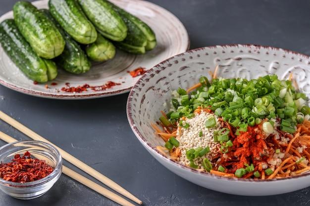 Producten voorbereiden voor het koken van traditionele koreaanse komkommerkimchi-snack: het mengen van ingrediënten in een kom, gefermenteerd voedsel, horizontale foto