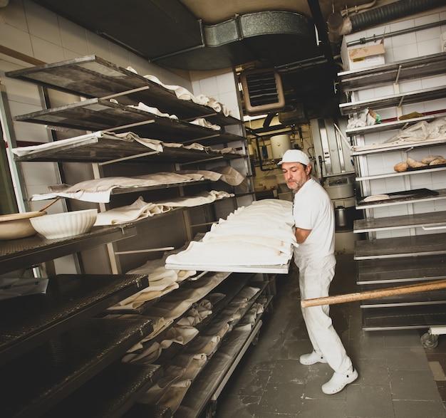 Productie van gebakken brood met een houtoven in een bakkerij.