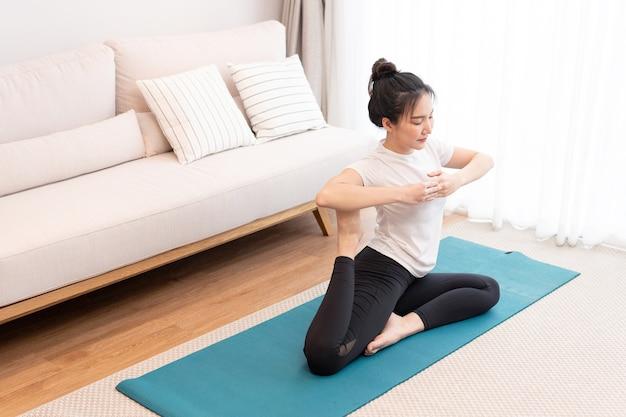 Productief activiteitenconcept een meisje met een knot die het witte t-shirt draagt, doet de moeilijke pilatesbeweging.