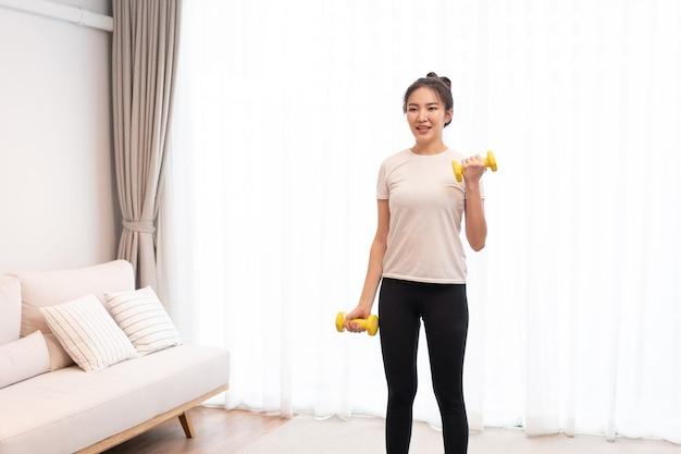 Productief activiteitenconcept een meisje met een knotje dat een wit t-shirt draagt en de gele halter opheft met haar rechterhand in haar leefruimte.