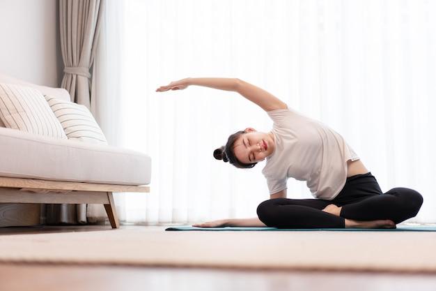 Productief activiteitenconcept een vrouwelijke jonge volwassene die een wit t-shirt draagt, oefent de flexibiliteit van haar lichaam door mat pilates te doen.