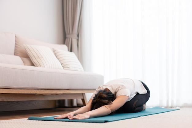 Productief activiteitenconcept in de woonkamer een meisje dat het lichaam gewillig evenwijdig aan de vloer buigt op de groene yogamat.