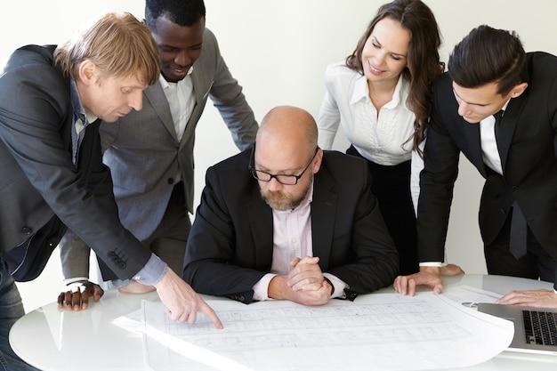 Productief teamwerk op kantoor. de hoofdingenieur in brillen luistert naar nieuwe ideeën van zijn collega. blanke man wijzende vinger op schematische tekeningen. collega's keuren zijn aanbod met een glimlach goed.