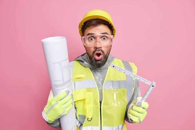 Productiefabriek ziet er verbijsterd uit houdt meetlint vast en blauwdruk komt op bouwplaats