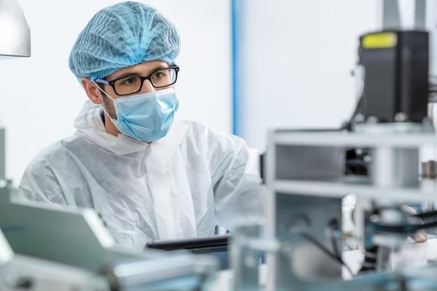 Productielijn werknemer met gezichtsmasker werken in elektronische fabriek
