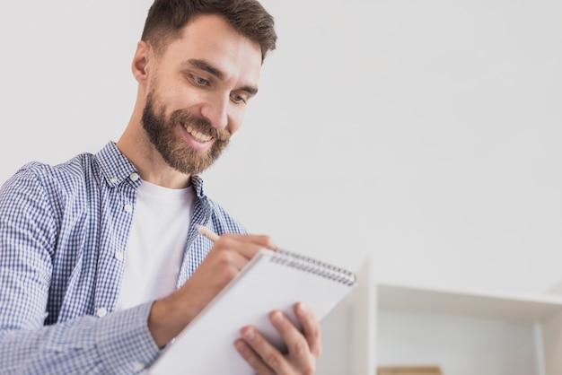 Productieve man schrijven in kladblok