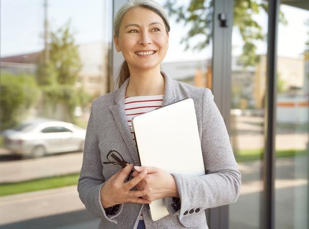Productieve werkdag gelukkige senior dame succesvolle volwassen zakenvrouw die laptop vasthoudt en kijkt