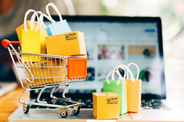 Productpakketdozen en boodschappentas in kar met laptop voor online het winkelen en leveringsconcept