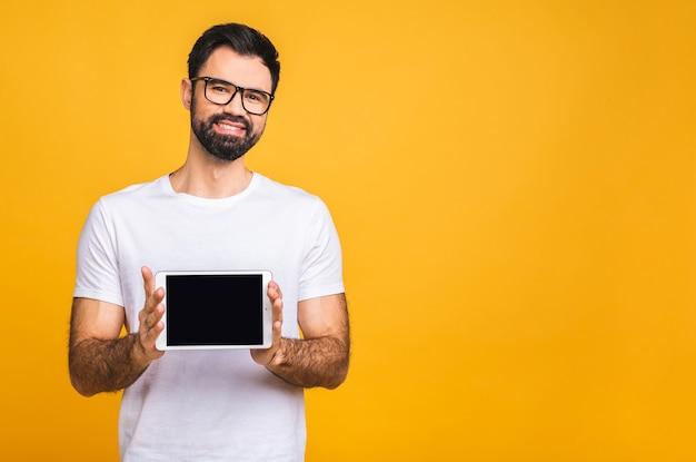 Productpresentatie. promotie. jonge, bebaarde man die in handen tabletcomputer met leeg scherm, close-up. geïsoleerd op gele achtergrond.