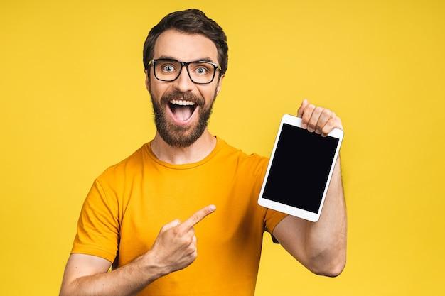 Productpresentatie. promotie. jonge, bebaarde man met in handen tabletcomputer met leeg scherm. geïsoleerd op gele achtergrond.