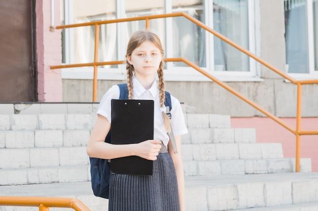 Productreclame. gelukkig klein schoolgaande kind dat uw product voorstelt. meisje met boeken die glimlachen en product of dienst voorstellen. je kunt nooit fout gaan met dit product.