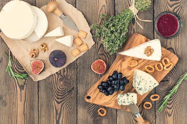 Proevende kaasschotel met kruiden en vruchten op houten lijst