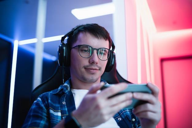 Professional boy gamer speelt mobiel spel op de slimme telefoon. hij draagt een koptelefoon en spreekt commando's in de microfoon.