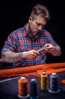 Professional leather worker vormt een nieuw leerproduct op zijn werkblad
