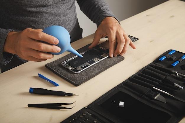 Professional werkt in zijn lab om de toolkit-box van de smartphone te repareren en schoon te maken met specifieke instrumenten in de buurt