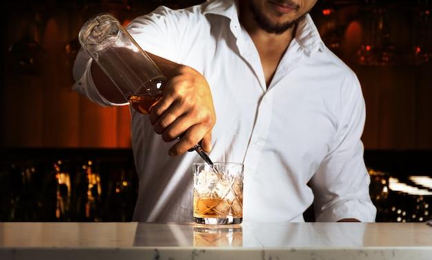 Professioneel aan de bar bereidt mixdrankjes voor zijn gasten. gemengde media